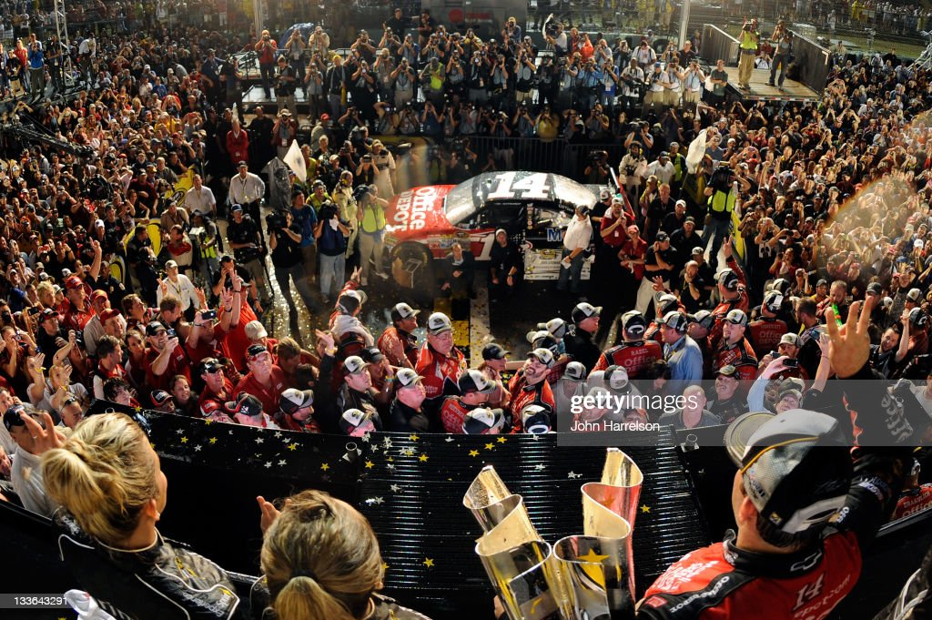 <a gi-track='captionPersonalityLinkClicked' href=/galleries/search?phrase=Tony+Stewart+-+Race+Car+Driver&family=editorial&specificpeople=201686 ng-click='$event.stopPropagation()'>Tony Stewart</a>, driver of the #14 Office Depot/Mobil 1 Chevrolet, celebrates with the Championship trophy in Victory Lane after winning the NASCAR Sprint Cup Series Ford 400 and the 2011 Series Championship at Homestead-Miami Speedway on November 20, 2011 in Homestead, Florida. Stewart wins his third NASCAR Championship.