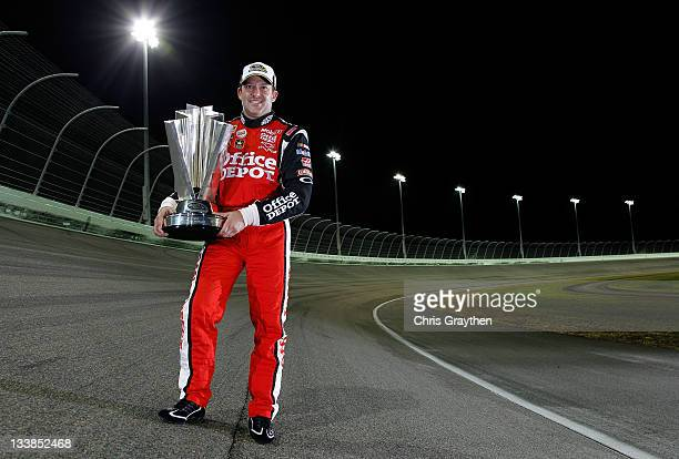 Tony Stewart driver of the Office Depot/Mobil 1 Chevrolet poses with the Championship trophy after winning the NASCAR Sprint Cup Series Ford 400 and...