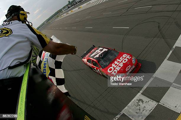 Tony Stewart driver of the Office Depot/Old Spice Chevrolet crosses the finish line to win the NASCAR Sprint Cup Series Pocono 500 on June 7 2009 at...