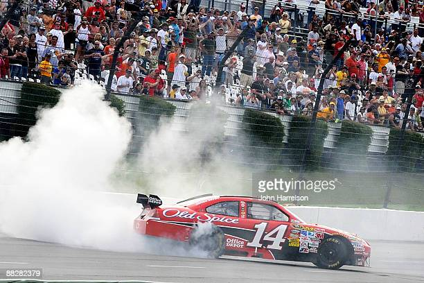 Tony Stewart driver of the Office Depot/Old Spice Chevrolet does a burnout after winning the NASCAR Sprint Cup Series Pocono 500 on June 7 2009 at...