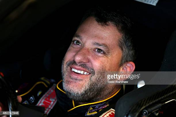 Tony Stewart driver of the Rush Truck Centers Chevrolet sits in his car in the garage area during practice for the NASCAR Sprint Cup Series Quaker...