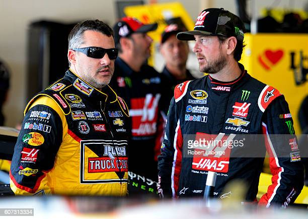 Tony Stewart driver of the Rush Truck Centers/Mobil 1 Chevrolet and Kurt Busch driver of the Haas Automation Chevrolet stand in the garage area...
