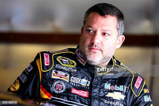 Tony Stewart driver of the Rush Truck Centers/Mobil 1 Chevrolet stands in the garage area during practice for the NASCAR Sprint Cup Series...