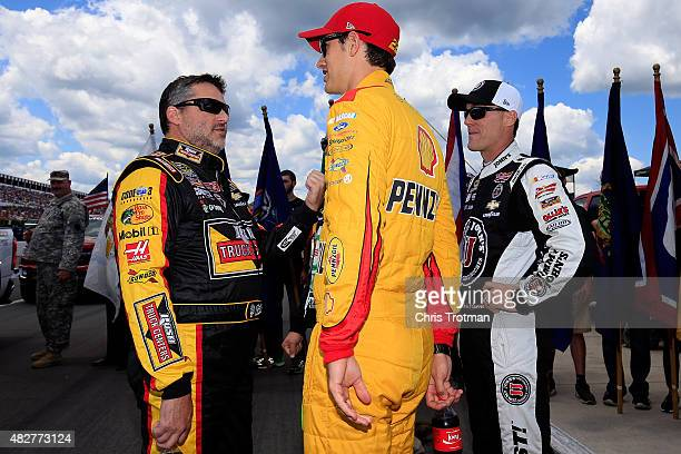 Tony Stewart driver of the Rush Truck Centers/Mobil 1 Chevrolet talks with Joey Logano driver of the Shell Pennzoil Ford and Kevin Harvick driver of...