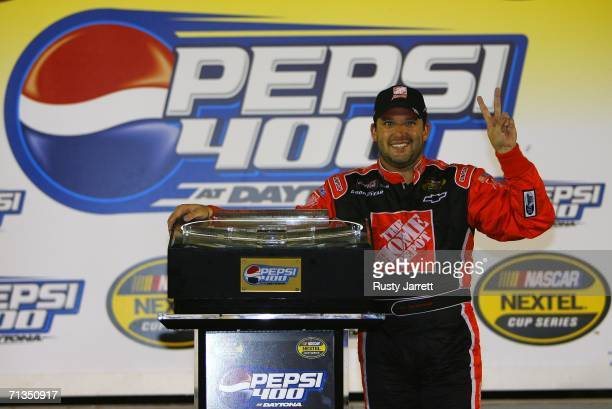 Tony Stewart driver of the The Home Depot celebrates his win in the flag stand after the NASCAR Nextel Cup Series Pepsi 400 on July 1 2006 at Daytona...