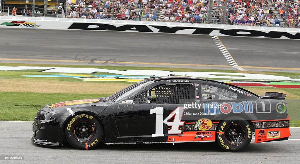 Tony Stewart drives his damaged race car, with the part of the number '14' formed with duct tape, down pit road during the Daytona 500 race at Daytona International Speedway in Daytona, Beach, Florida, Sunday, February 24, 2013.