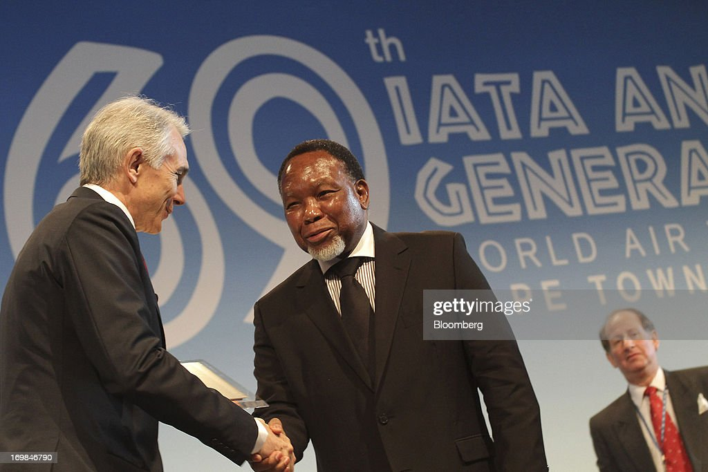 Tony Tyler, chief executive officer of the International Air Transport Association (IATA), left, shakes hands with Kgalema Motlanthe, South Africa's deputy president, during the company's annual general meeting in Cape Town, South Africa, on Monday, June 3, 2013. Airline earnings will be 20 percent higher this year than forecast just three months ago as capacity cuts help pack planes to record levels, the International Air Transport Association said today. Photographer: Nadine Hutton/Bloomberg via Getty Images