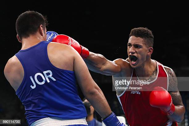 Tony Victor James Yoka of France throws a right on Hussein Iashaish of Jordan in the boxing Men's Super Heavy Quarterfinal 1 on Day 11 of the Rio...