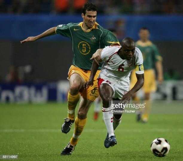 Tony Vidmar of Australia fights for the ball with Hatem Trabelsi of Tunisia during the match between Australia and Tunisia for the FIFA...
