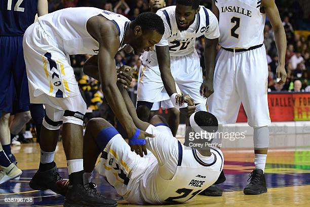 Tony Washington and BJ Johnson help up Jordan Price all of the La Salle Explorers during the second half at Tom Gola Arena on January 15 2017 in...