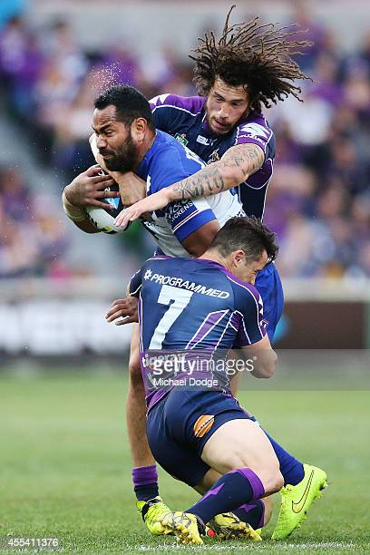 Tony Williams of the Bulldogs is tackled by Cooper Cronk and Kevin Proctor of the Storm during the NRL 2nd Elimination Final match between the...