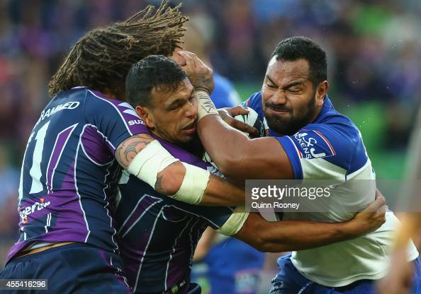 Tony Williams of the Bulldogs is tackled by Kevin Proctor and Will Chambers of the Storm during the NRL 2nd Elimination Final match between the...
