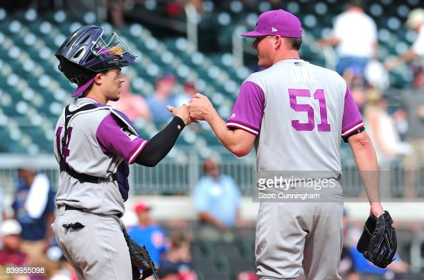 Tony Wolters and Jake McGee of the Colorado Rockies celebrate after the game against the Atlanta Braves at SunTrust Park on August 27 2017 in Atlanta...
