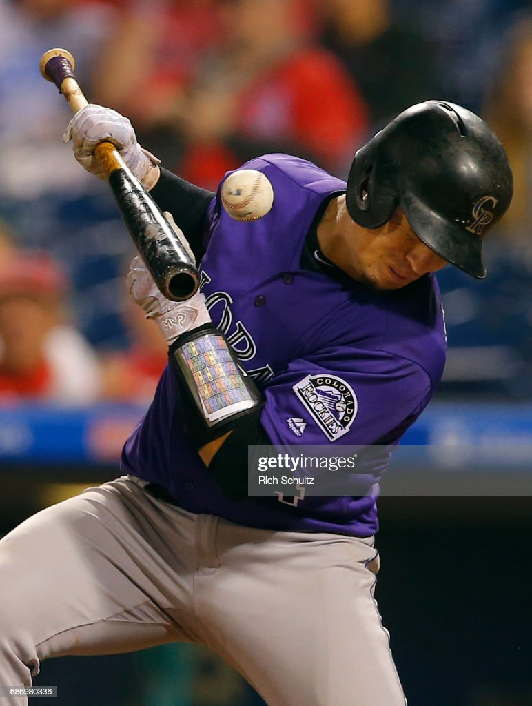 Tony Wolters #14 of the Colorado Rockies is hit in the chest by a pitch while attempting to sacrifice in the eighth inning of a game against the Philadelphia Phillies at Citizens Bank Park on May 22, 2017 in Philadelphia, Pennsylvania.
