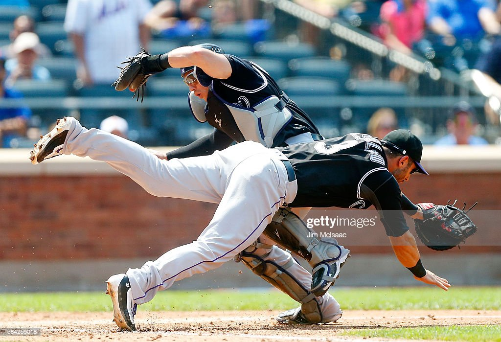 Tony Wolters #14 of the Colorado Rockies makes a catch on a pop up in the fourth inning against the New York Mets as he collides with teammate Daniel Descalso #3 at Citi Field on July 28, 2016 in the Flushing neighborhood of the Queens borough of New York City.