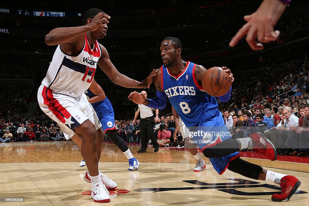 Tony Wroten of the Philadelphia 76ers drives against Kevin Seraphin of the Washington Wizards during the game at the Verizon Center on November 1...