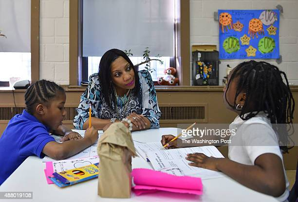 Tonya Herron a volunteer tutor works with Ayanna Anderson left and Ardriana Simpson on their school work during the after school program at the...