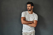 Handsome young man looking away and keeping arms crossed while standing against grey background