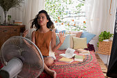 Sweating Asian girl cooling herself with big fan