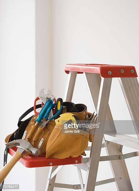 Tool belt on ladder shelf