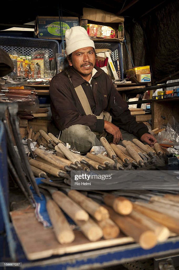 A tool vendor with his traditional blacksmith crafted tools in makeshift stall at the back of his pick up truck in Kintamani market.