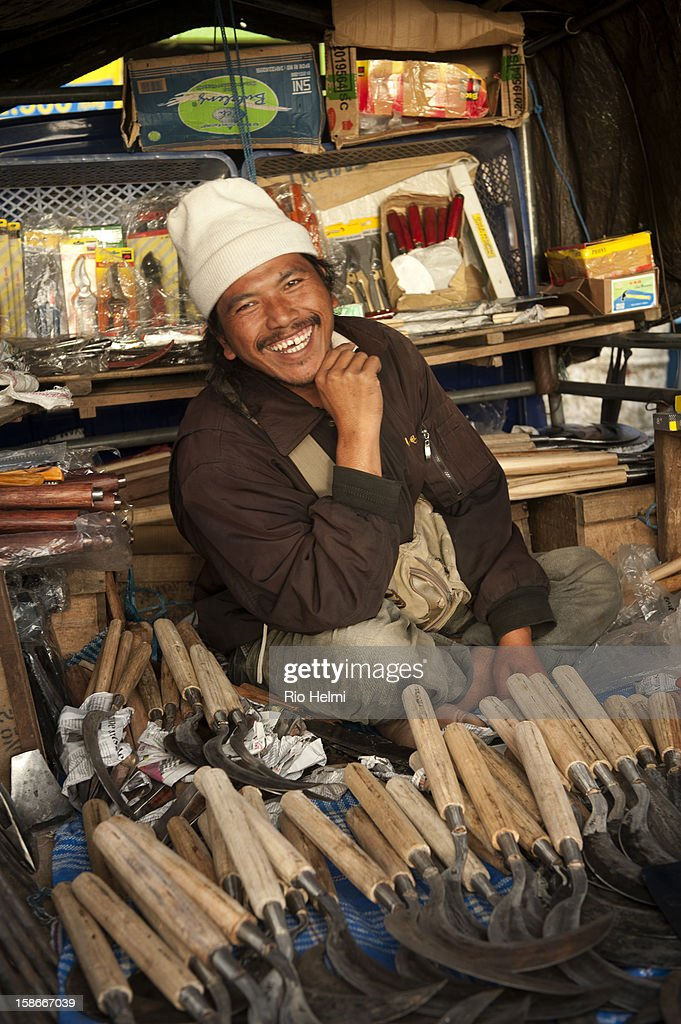 MARKET, KINTAMANI, BALI, INDONESIA - : A tool vendor with his traditional blacksmith crafted tools in makeshift stall at the back of his pick up truck in Kintamani market.