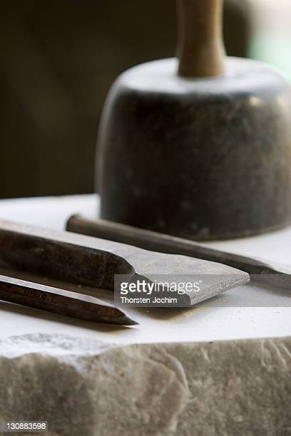 Tools from a hewer on white marble. Mallet and black chisel.