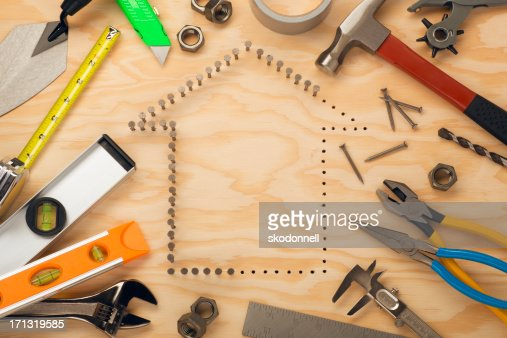Tools surrounding nails in house shape