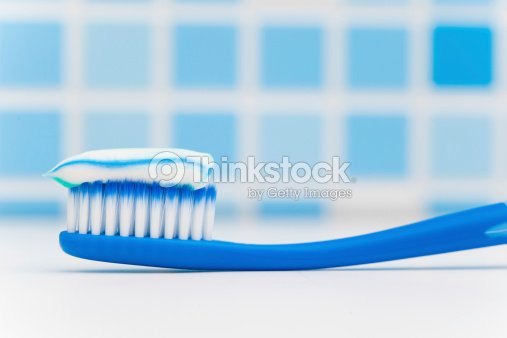 toothbrush against blue tile background : Stock Photo