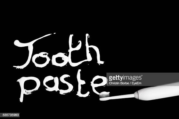 Toothpaste Written From Toothbrush Over Black Background