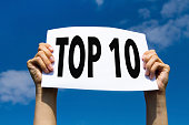 top 10, hands holding sign in blue sky