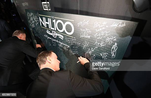 Top 100 player Joe Nieuwendyk signs a poster board backstage during the NHL 100 presented by GEICO show as part of the 2017 NHL AllStar Weekend at...