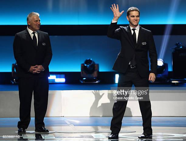 Top 100 player Luc Robitaille waves to the audience as Brett Hull looks on during the NHL 100 presented by GEICO show as part of the 2017 NHL AllStar...