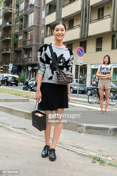 Top Chinese model Liu Wen exits Gucci in a MoCo x Lane Crawford sweatshirt and Gucci bag on Day 1 of Milan Fashion Week Spring/Summer 2015 on...
