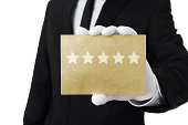 Human hand holding gold card with five stars on it