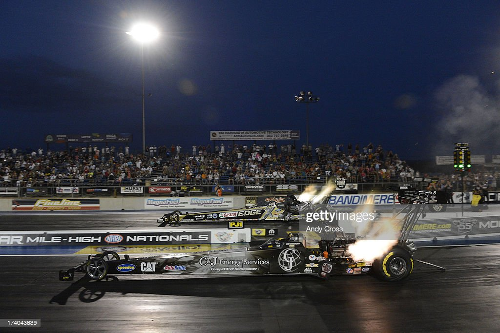 Top Fuel drag racers, Brittney Force, top, and Bob Vandergriff, take off during qualifying at the Mopar Mile-High Nationals Friday evening at Bandimere Speedway, July 19, 2013.