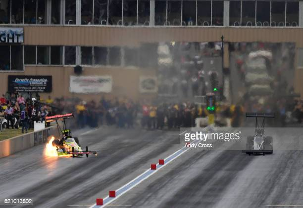 NHRA top fuel driver Troy Coughlin left has an engine let go heading down track against Steve Chrisman at the 38th annual NHRA Mopar Mile High...