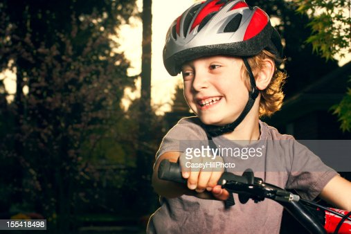 Top half of a smiling young boy riding a bike outside