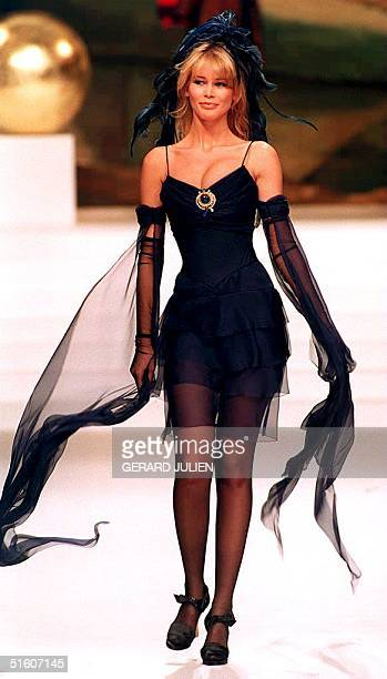 Top model Claudia Schiffer displays a long muslin cocktail dress with veil sleeves 15 January 1994 during the presentation of 1994 SpringSummer...