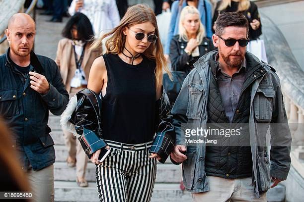 Top model Gigi Hadid wears circular sunglasses a patent leather jacket off her shoulders a blue sleeveless top and black and white striped pants...
