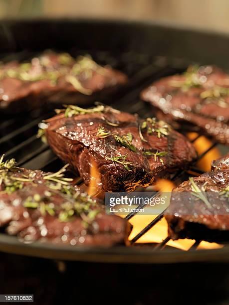 Top Sirloin Steaks with Fresh Herbs on an outdoor BBQ