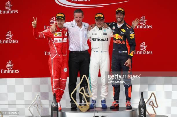 Top three finishers Valtteri Bottas of Finland and Mercedes GP Sebastian Vettel of Germany and Ferrari and Daniel Ricciardo of Australia and Red Bull...