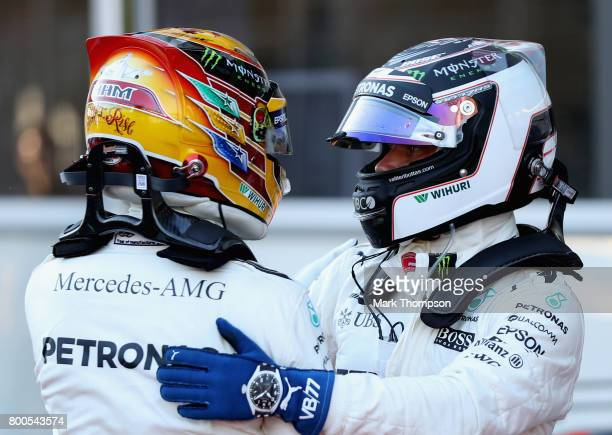 Top two qualifiers and team mates Lewis Hamilton of Great Britain and Mercedes GP and Valtteri Bottas of Finland and Mercedes GP embrace in parc...