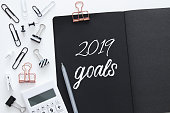 Top view 2019 goals list with notebook and calculator over wooden white desk