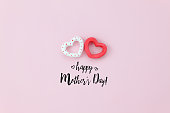 Top view aerial image of decoration Happy mother's day holiday background concept.Flat lay sign of season couple heart shape on pink paper at home office desk with creative design text for seasonal.