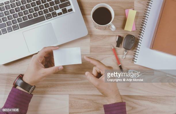 Top view business card blank in man's hand pointing with index finger office desk
