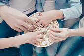 Top view close up portrait of hands taking sweet pop corn from bucket, dad mom kids sharing popcorn while watching film program tv, sitting on sofa indoor, enjoying free time having fun