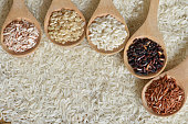 Top view different rice on wooden spoon