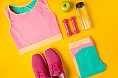 Still life of bottle with water, sportswear, dumbbells, apple on yellow background. Top view, flat lay. Mockup Sports and fitness background.