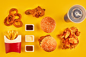 Top view hamburger, french fries and fried chicken on yellow background. Copy space for your text. Still life. Flat lay. Menu or receipt background